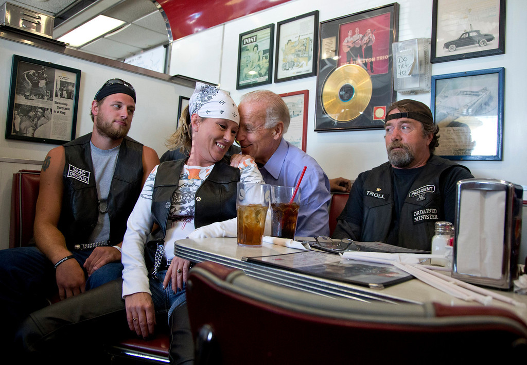 Description of . In this Sept. 9, 2012 file photo, Vice President Joe Biden talks to customers at Cruisers Diner during a campaign stop in Seaman, Ohio. The unidentified woman pulled her chair up close to the bench that Biden was seated on in order to speak to him. (AP Photo/Carolyn Kaster, File)