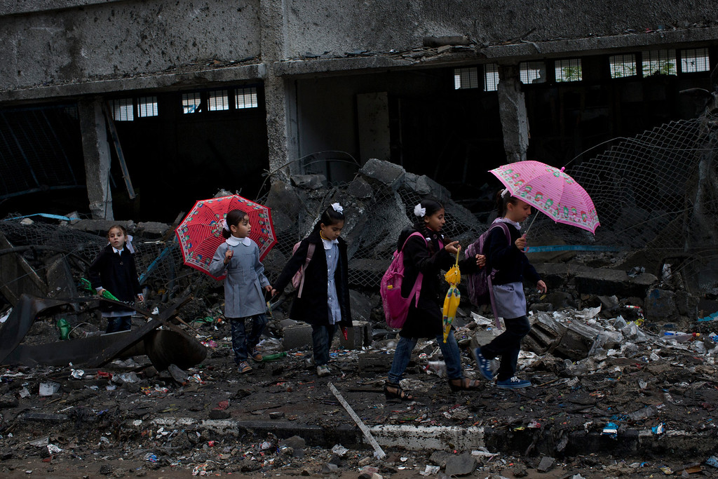 Description of . In this Nov. 24, 2012 file photo, Palestinian schoolchildren walk between debris of a damaged school in Gaza City. The school was damaged when Israeli forces struck on a nearby building. This photo was one in a series of images by Associated Press photographer Bernat Armangue that won the first place prize in the World Press Photo 2013 photo contest for the Spot News series category. (AP Photo/Bernat Armangue, File)