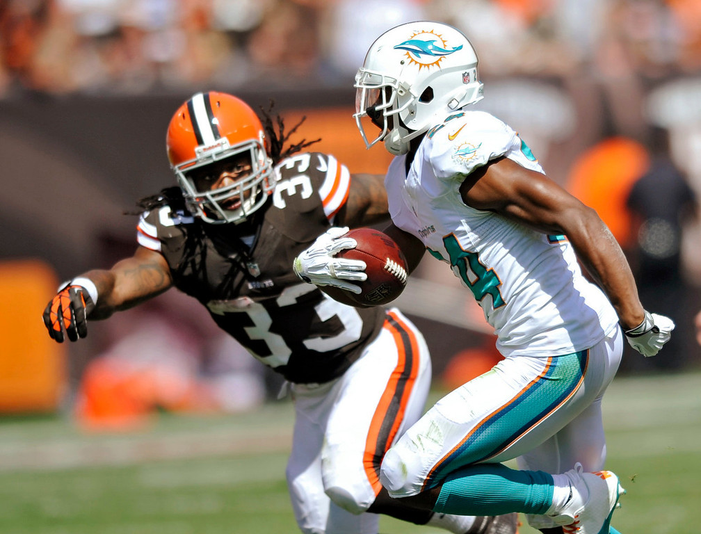Description of . Miami Dolphins cornerback Dimitri Patterson is chased by Cleveland Browns running back Trent Richardson (33) after Patterson intercepted a pass in the second quarter of an NFL football game Sunday, Sept. 8, 2013, in Cleveland. (AP Photo/David Richard)