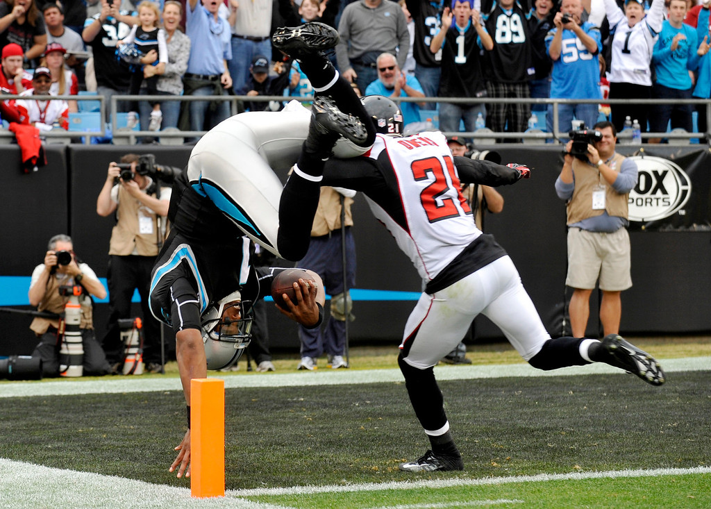 . Carolina Panthers quarterback Cam Newton (1) dives into the end zone for a touchdown as Atlanta Falcons\' Chris Owens (21) pursues during the second half of an NFL football game in Charlotte, N.C., Sunday, Dec. 9, 2012. (AP Photo/Rainier Ehrhardt)