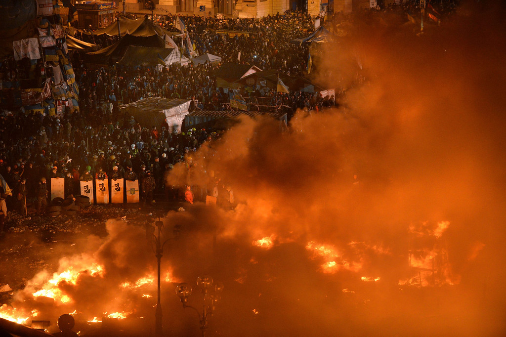 Description of . Anti-government protesters clash with the police during their storming of Independence Square in Kiev on February 18, 2014. Flames engulfed the main anti-government protest camp on Kiev's Independence Square as riot police tried to force demonstrators out following the bloodiest clashes in three months of protests. The iconic square turned into a war zone as riot police moved slowly through opposition barricades from several directions, hurling stun grenades and using water cannon to clear protestors.    AFP PHOTO/SERGEI  SUPINSKY/AFP/Getty Images