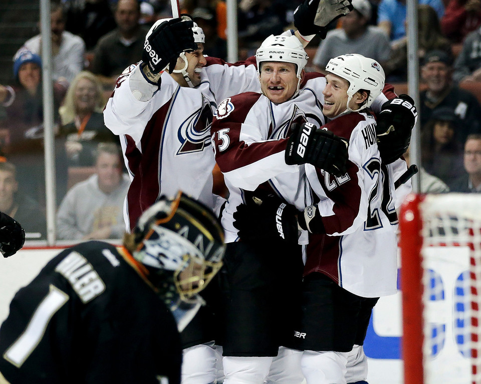 Description of . Colorado Avalanche left wing Cody McLeod, center, celebrates his goal with defenseman Matt Hunwick, right, and left wing Patrick Bordeleau as Anaheim Ducks goalie Jonas Hiller looks down during the first period of an NHL hockey game in Anaheim, Calif., Sunday, Feb. 24, 2013. (AP Photo/Chris Carlson)