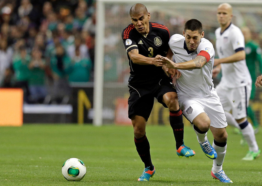 Description of . Mexico's Carlos Salcido, left, and United States captain Clint Dempsey vie for the ball during a 2014 World Cup qualifying match at the Aztec stadium in Mexico City, Tuesday, March 26, 2013. (AP Photo/Eduardo Verdugo)