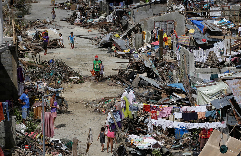 Description of . Survivors of Typhoon Haiyan walk amid ruins of their homes in Maraboth, Philippines, Thursday, Nov. 14, 2013. (AP Photo/Dita Alangkara)