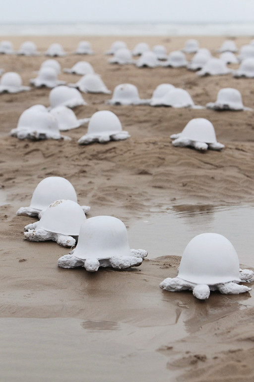 Description of . A picture taken in Colleville-sur-Mer Beach on June 5, 2011,shows part of the installation by French artist Rachid Khimoune of 1.000 turtle-shaped statues made in the 90's from diferent countries helmets. The statues, exhibited here on the 67th D-Day anniversary on June 6, 1944 allied landings in Normandy, then occupied by Nazi Germany, aim at symbolizing