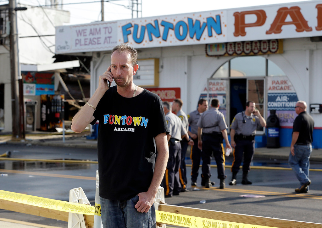 Description of . Daniel Shauger, manager of the Funtown Arcade, talks on the phone near the establishment the morning after a massive fire burned a large portion of the Seaside Park boardwalk including the arcade, Friday, Sept. 13, 2013, in Seaside Park, N.J. (AP Photo/Julio Cortez)