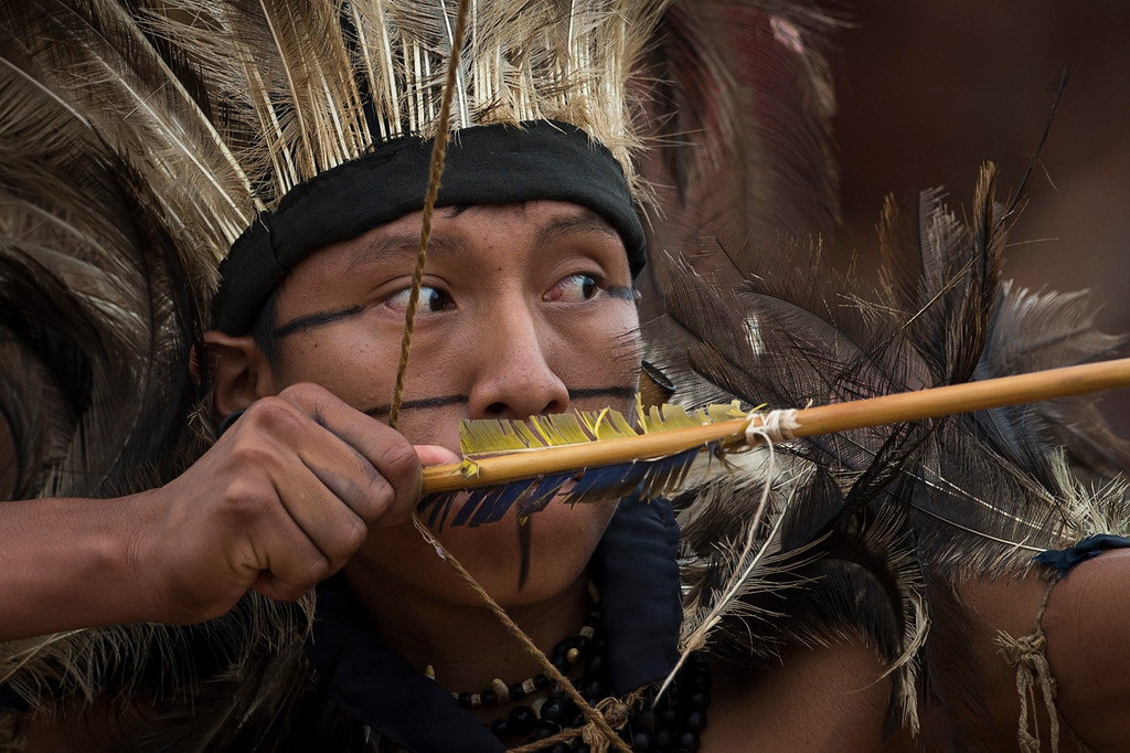 Description of . A Terena Indian takes aim in the bow and arrow competition during the indigenous games in Cuiaba, Brazil, Tuesday, Nov. 12, 2013. (AP Photo/Felipe Dana)