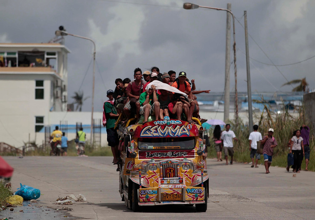 Description of . Survivors ride an overloaded passenger jeepney as they flee typhoon-hit Tacloban city, Leyte province, central Philippines on Wednesday, Nov. 13, 2013. Typhoon Haiyan, one of the strongest storms on record, slammed into six central Philippine islands on Friday leaving a wide swath of destruction. (AP Photo/Aaron Favila)