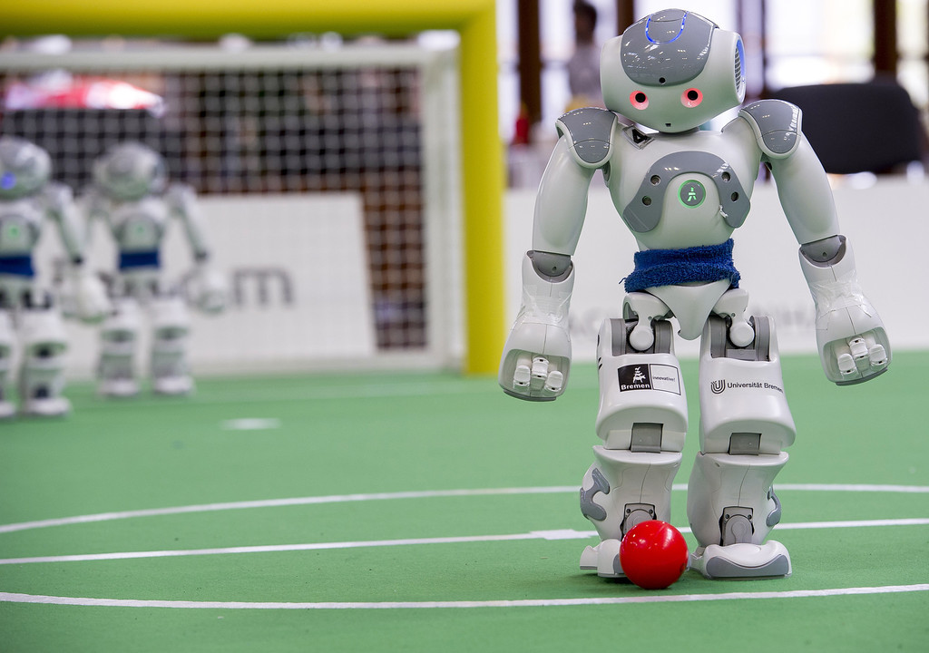 Description of . MAGDEBURG, GERMANY - APRIL 26:  Two teams of robots play against each other in soccer at the 2013 RoboCup German Open tournament on April 26, 2013 in Magdeburg, Germany. The robots, which are a model called Nao, manufactured by Aldebaran Robotics, perform autonomously and communicate with one another via WLAN. The three-day tournament is hosting 43 international teams and 158 German junior teams that compete in a variety of disciplines, including soccer, rescue and dance.  (Photo by Jens Schlueter/Getty Images)