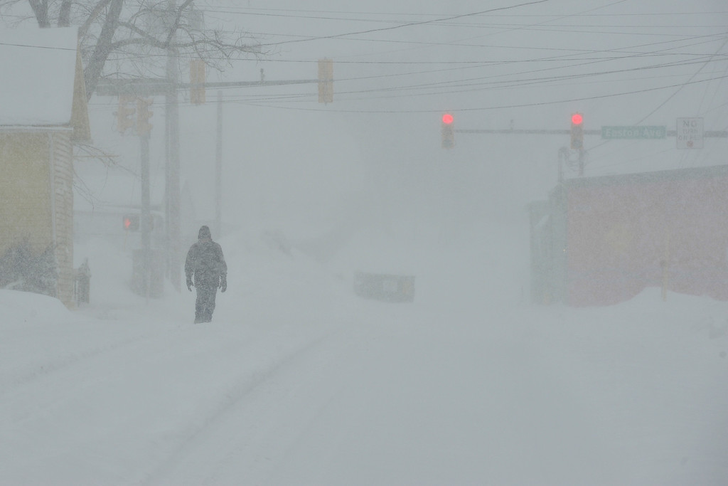 Description of . A man walks along Farmersville road near Green Pond road Thursday, February 13, 2014 in Bethlehem Township, Pa. A winter storm dumps heavy snow across the Lehigh Valley making driving very difficult. (AP Photo/Chris Post)