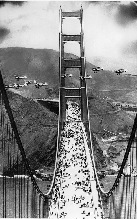 Description of . Military biplanes fly between the towers of the Golden Gate Bridge as pedestrians walk across the span during opening ceremonies in San Francisco on May 27, 1937.  (AP Photo)