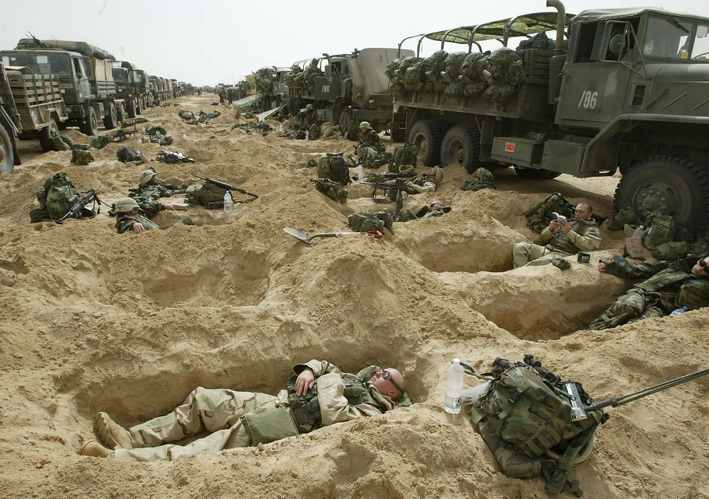 Description of . Soldiers from the 3rd Brigade of the U.S. 101st Airborne Division rest in fox holes by their convoy staging area in the Kuwaiti desert Friday, March 21, 2003. Allied force missions continued as combat units rumbled across the desert into Iraq from the south and bombed limited targets in Baghdad. (AP Photo/Jean-Marc Bouju)