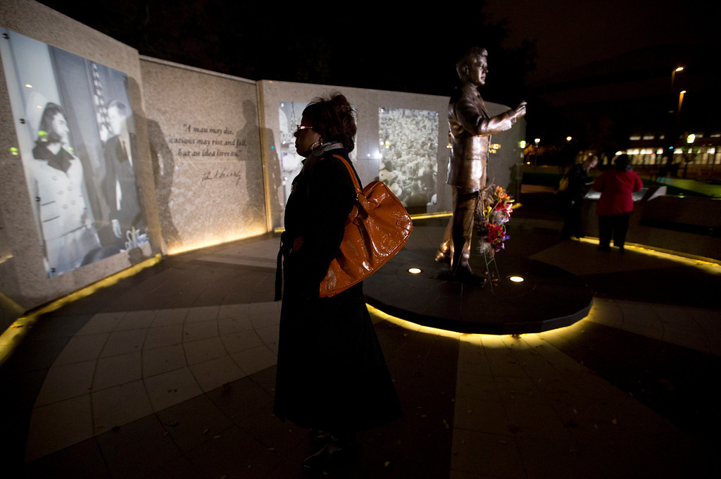 Description of . Brenda Murphy of Fort Worth pauses at the JFK Tribute outside the Hilton Hotel on the 50th anniversary of the John F. Kennedy's assassination, Friday, Nov. 22, 2013.  The 50th anniversary is being marked today in Dallas, where Kennedy was shot, and elsewhere in the United States and overseas.  (AP Photo/The Fort Worth Star-Telegram, Joyce Marshall)
