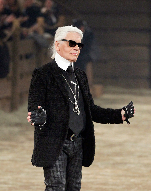 Description of . Chanel designer Karl Lagerfeld takes a bow at the end of his Metiers d'Art fashion show, Tuesday, Dec. 10, 2013, in Dallas. For more than a decade, designer Lagerfeld has picked a city linked to the house for the theme of the show staged each December to highlight the work of its artisans. Fashion house founder Gabrielle