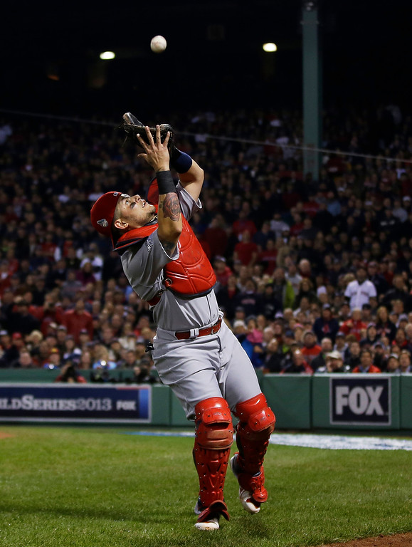 Description of . St. Louis Cardinals catcher Yadier Molina catches a pop up by Boston Red Sox shortstop Xander Bogaerts during the second inning of Game 6 of baseball's World Series Wednesday, Oct. 30, 2013, in Boston. (AP Photo/Matt Slocum)