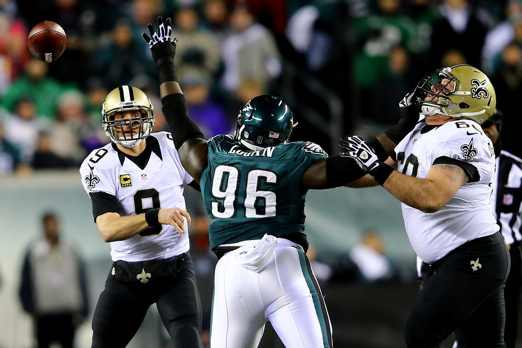Description of . PHILADELPHIA, PA - JANUARY 04:  Drew Brees #9 of the New Orleans Saints throws a pass in the first quarter against Bennie Logan #96 of the Philadelphia Eagles during their NFC Wild Card Playoff game at Lincoln Financial Field on January 4, 2014 in Philadelphia, Pennsylvania.  (Photo by Al Bello/Getty Images)