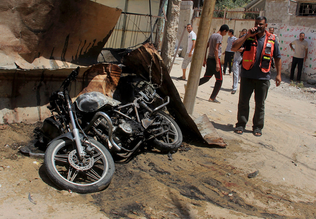 Description of . A Palestinian medic inspects the wreckage of a motorcycle caused by an Israeli airstrike in Rafah on Thursday, July 31, 2014. Fadel Elmeghary, an Islamic Jihad member, was killed in the airstrike, while on his motorcycle in Rafah, according to Gaza health official Ashraf al-Kidra. (AP Photo/Hatem Ali)