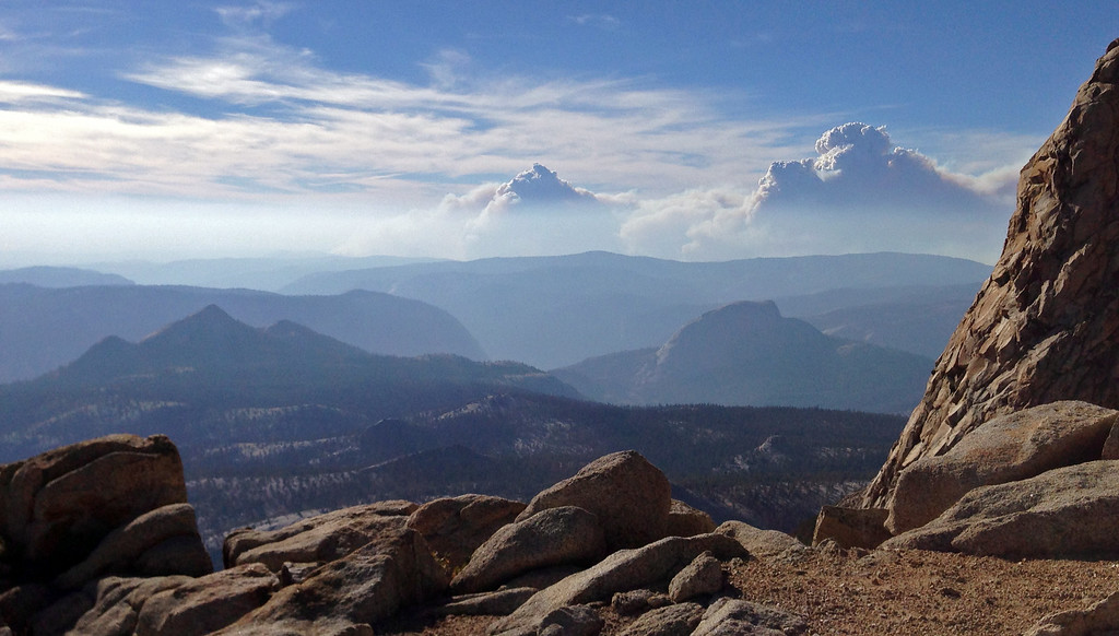 Description of . Smoke clouds and bands of haze from the Rim Fire in the western Sierra Nevada loom up some 20 miles behind the famed granite monolith known as Half Dome, right center, seen from 11,500-foot Mt. Clark in Yosemite Valley in Yosemite National Park, Calif., Saturday, Aug. 24, 2013. Crews working to contain one of California's largest-ever wildfires gained some ground Monday against the flames threatening San Francisco's water supply, several towns near Yosemite National Park and historic giant sequoias. Containment of the Rim Fire more than doubled to 15 percent, although it was within a mile of the park's Hetch Hetchy Reservoir, the source of San Francisco's famously pure drinking water, officials said Monday. (AP Photo/Tami Abdollah)