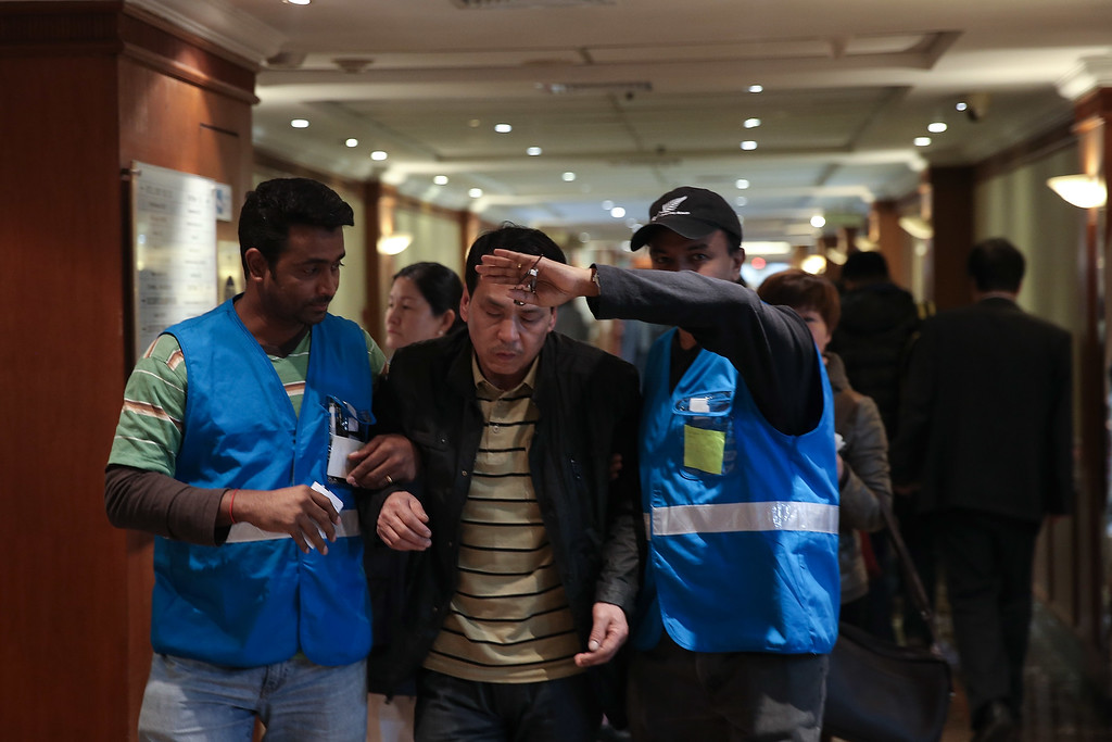 Description of . Malaysia Airline special assistance team members help a relative of a passenger onboard Malaysia Airlines flight MH370 at Lido Hotel on March 11, 2014 in Beijing, China. (Photo by Lintao Zhang/Getty Images)