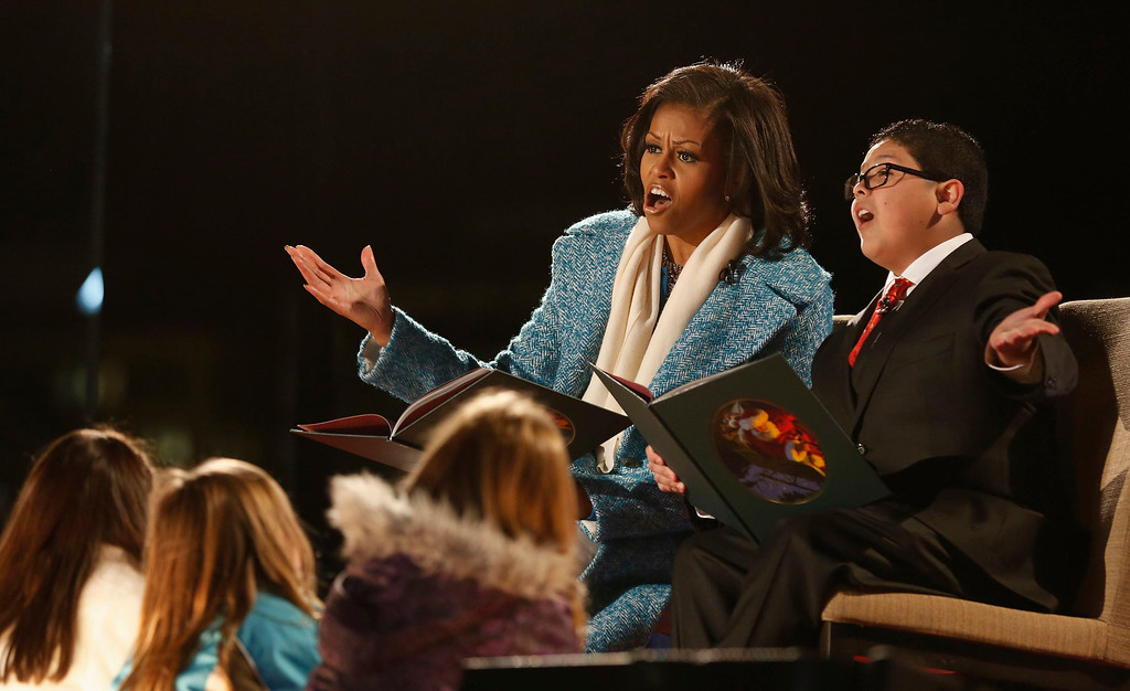 Description of . First lady Michelle Obama and actor Rico Rodriguez (R) read a Christmas carol to children at the official lighting of the National Christmas Tree ceremony on the Ellipse in Washington, December 6, 2012.     REUTERS/Larry Downing