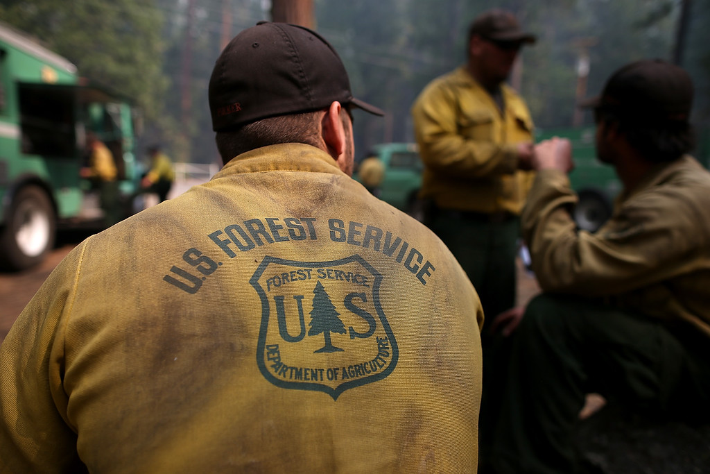Description of . Forest Service firefighters take a break from battling the Rim Fire at Camp Mather on August 25, 2013 near Groveland, California.  (Photo by Justin Sullivan/Getty Images)