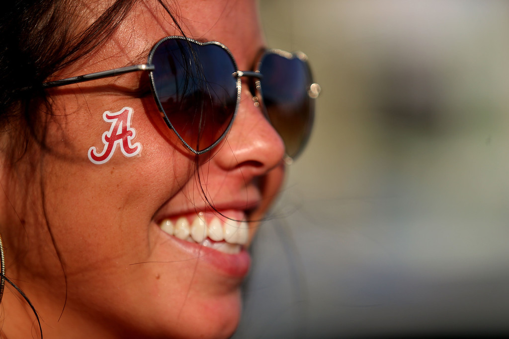 Description of . MIAMI GARDENS, FL - JANUARY 07:  An Alabama fan smiles before the 2013 Discover BCS National Championship game between the Alabama Crimson Tide and the Notre Dame Fighting Irish at Sun Life Stadium on January 7, 2013 in Miami Gardens, Florida.  (Photo by Mike Ehrmann/Getty Images)