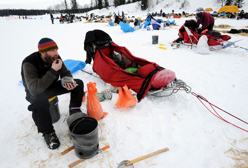 Description of . Mike Ellis eats breakfast while resting his dog team at the Finger Lake checkpoint in Alaska during the Iditarod Trail Sled Dog Race on Monday, March 4, 2013. (AP Photo/The Anchorage Daily News, Bill Roth)