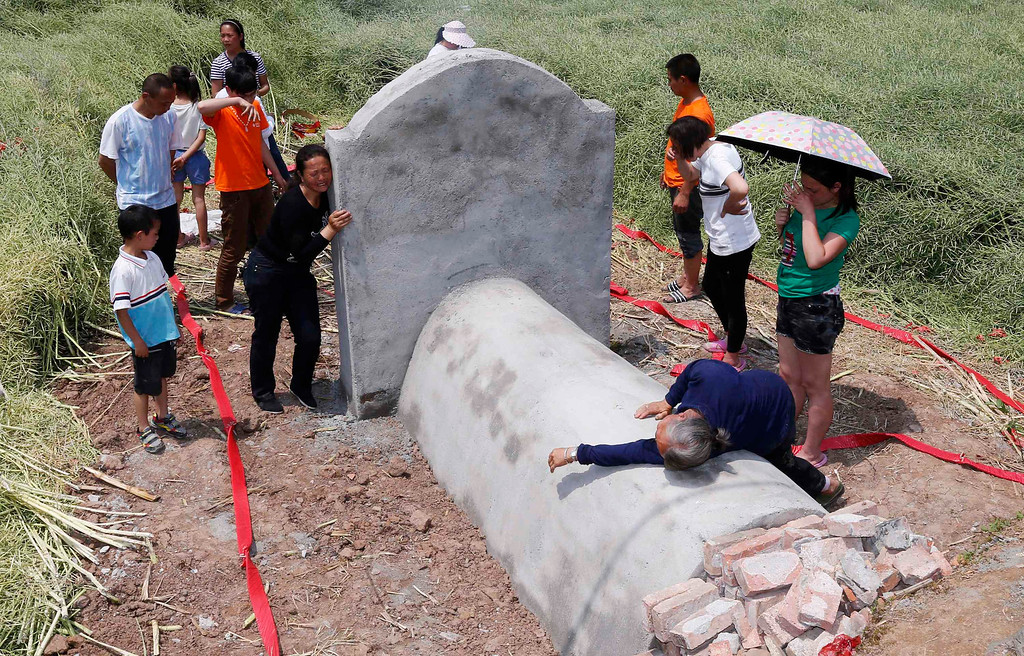 Description of . People cry as they mourn at the tomb of their relative who was killed in last Saturday's earthquake, in Longmen township of Lushan county, Sichuan province April 26, 2013. Friday marks the seventh day since the earthquake, an important day in China's traditional mourning process which lasts up to seven weeks. The earthquake has left 196 dead, 21 missing and more than 11,000 injured, according to Xinhua News Agency. REUTERS/Stringer