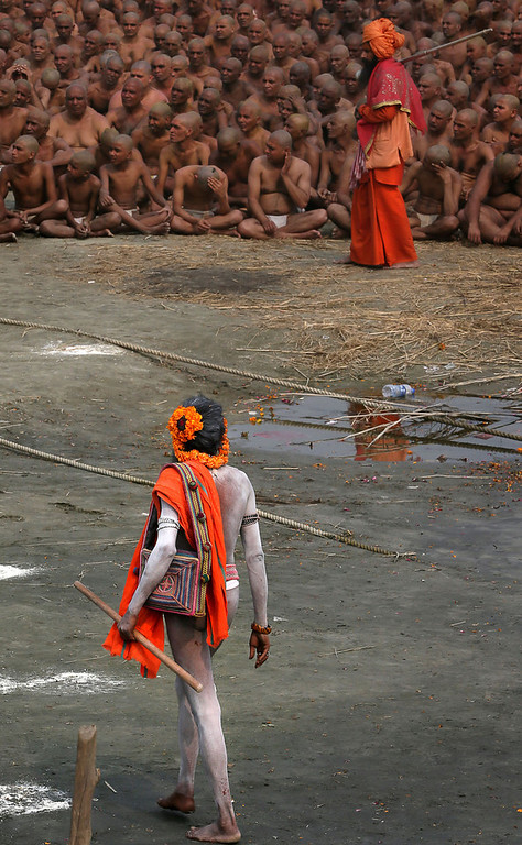 Description of . A Naga Sadhu, foreground, walks past Hindu holy men of the Juna Akhara sect participate in rituals that are believed to rid them of all ties in this life and dedicate themselves to serving God as a