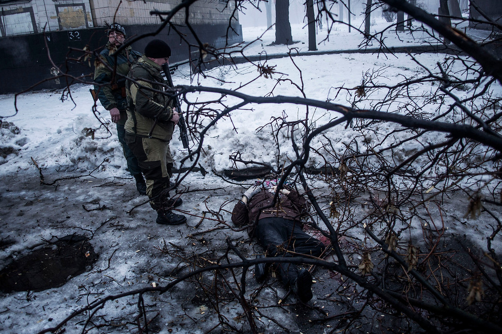 Description of . Separatist rebels look at the body of a man killed near a bus stop that was hit by Ukrainian army shells in Donetsk, eastern Ukraine, Tuesday, Jan. 20, 2015. At least three civilians were killed in shelling Tuesday in eastern Ukraine as fighting continued between government and rebel forces in the separatist-held city of Donetsk.  (AP Photo/Manu Brabo)