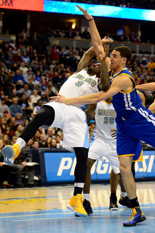 Description of . Golden State Warriors shooting guard Klay Thompson (11) fouls Denver Nuggets point guard Ty Lawson (3) during the first half at the Pepsi Center on Sunday, January 13, 2013. AAron Ontiveroz, The Denver Post