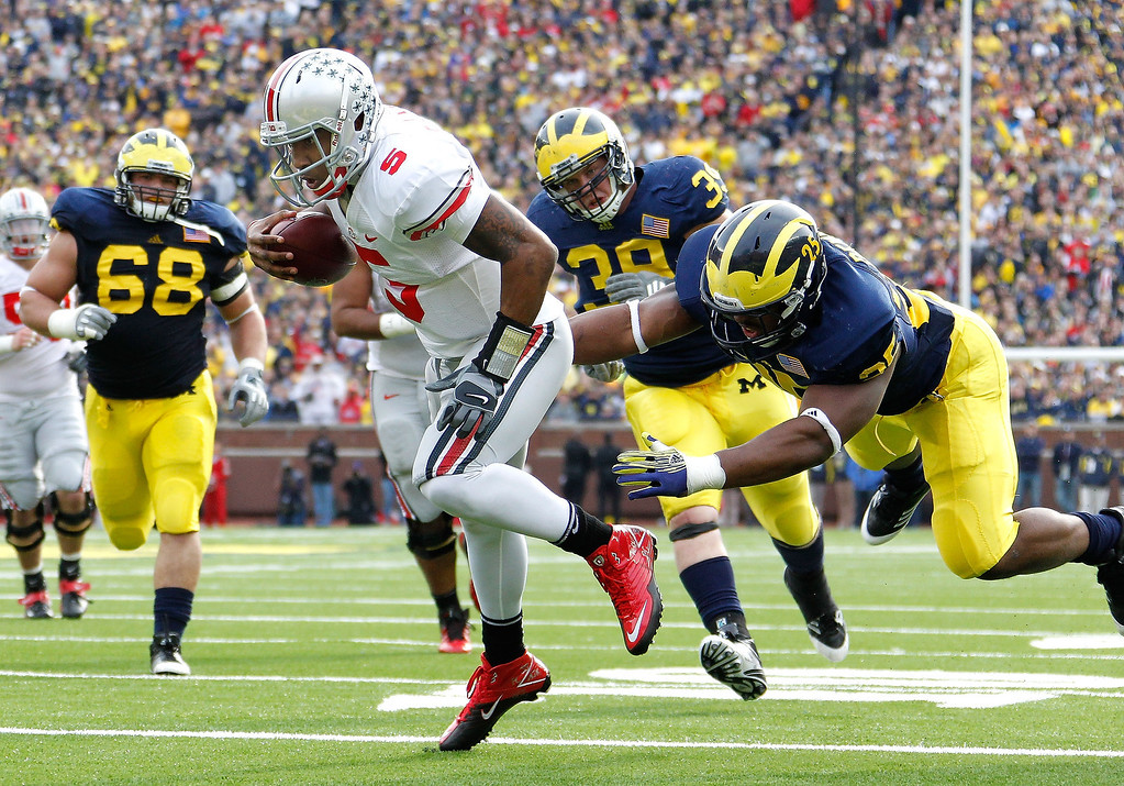 Description of . Braxton Miller #5 of the Ohio State Buckeyes gets in for a second quarter touchdown past Kenny Demens #25 of the Michigan Wolverines at Michigan Stadium on November 26, 2011 in Ann Arbor, Michigan. (Photo by Gregory Shamus/Getty Images)