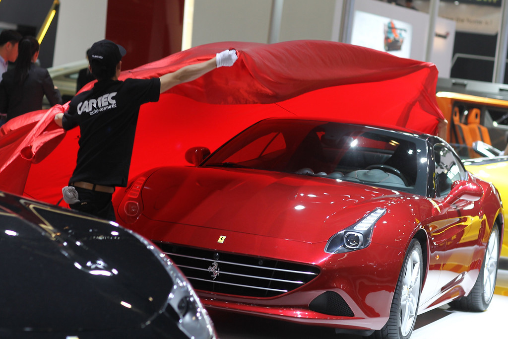 Description of . A staff unveils a Porsche car on display at the China International Exhibition Center new venue during the