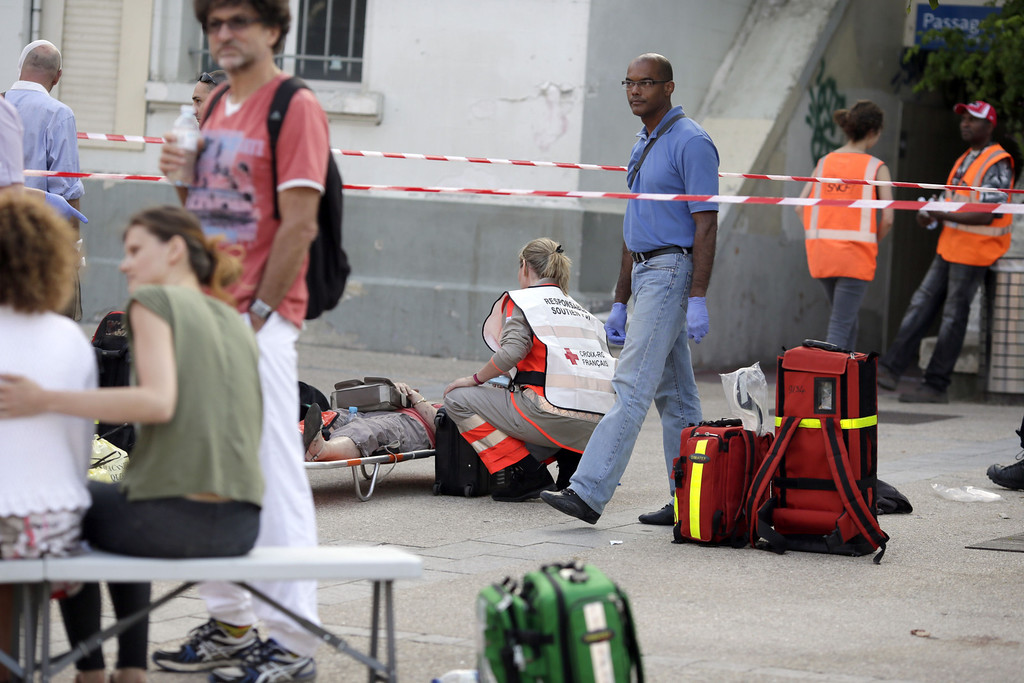 Description of . A Red Cross worker attends to a person on a stretcher at the site of a train accident in the railway station of Bretigny-sur-Orge, near Paris, on July 12, 2013. AFP PHOTO / POOL / KENZO TRIBOUILLARD/AFP/Getty Images