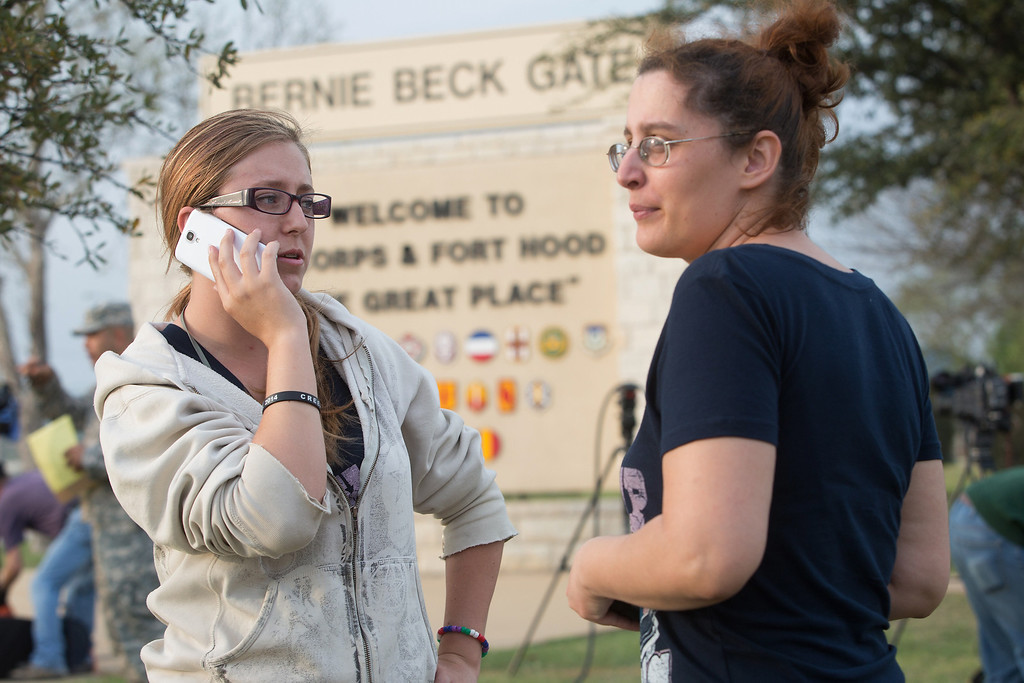 Description of . Krystina Cassidy and Dianna Simpson attempt to make contact with their husbands who are stationed inside Fort Hood, while standing outside of the Bernie Beck Gate, on Wednesday, April 2, 2014, in Fort Hood, Texas. At least one person was killed and 14 injured in a shooting Wednesday at Fort Hood, and officials at the base said the shooter is believed to be dead. (AP Photo/ Tamir Kalifa)
