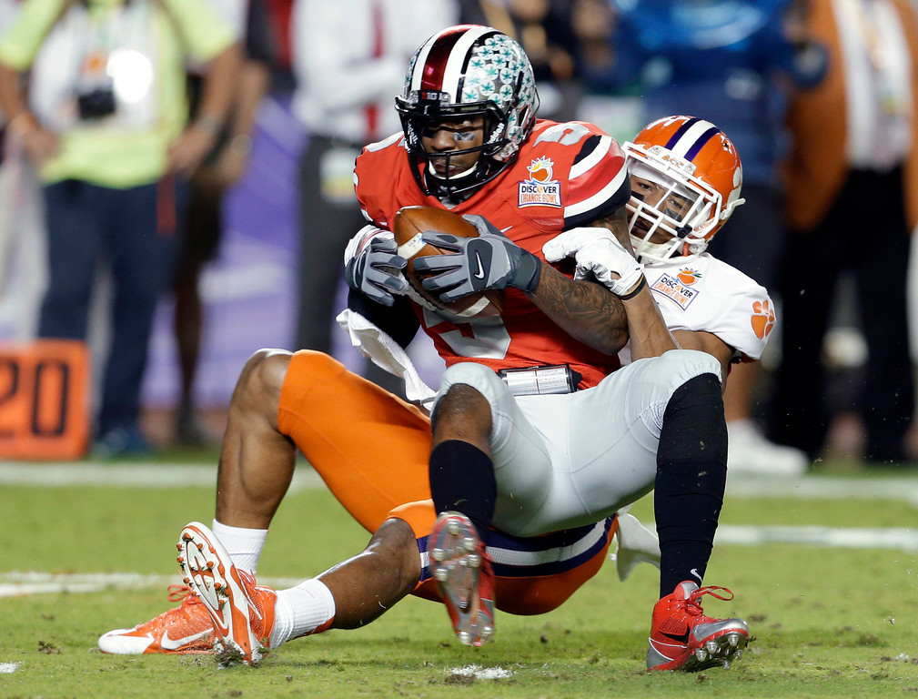 Description of . Ohio State quarterback Braxton Miller is brought down by Clemson defensive end Vic Beasley during the first half of the Orange Bowl NCAA college football game, Friday, Jan. 3, 2014, in Miami Gardens, Fla. (AP Photo/Lynne Sladky)