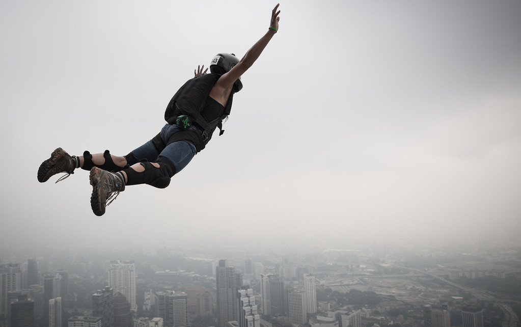 Description of . Base jumper Katherine Donahue from the US leaps from the 300-meters Open Deck of the Malaysia's landmark Kuala Lumpur Tower during the International Tower Jump in Kuala Lumpur on September 27, 2013.  AFP PHOTO / MOHD RASFAN/AFP/Getty Images
