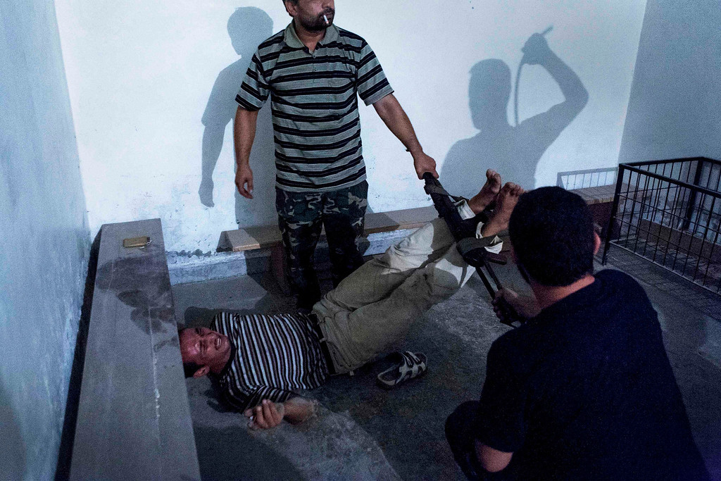 Description of . Emin Ozmen of Turkey has won the second prize in the Spot News Single category of the World Press Photo Contest 2013 with this picture of Syrian opposition fighters interrogating and torturing an informant in Aleppo taken on July 31, 2012 and distributed by the World Press Photo Foundation February 15, 2013. The prize-winning entries of the World Press Photo Contest 2013, the world's largest annual press photography contest, were announced today, February 15, 2013.  REUTERS/Emin Ozmen/World Press Photo/Handout