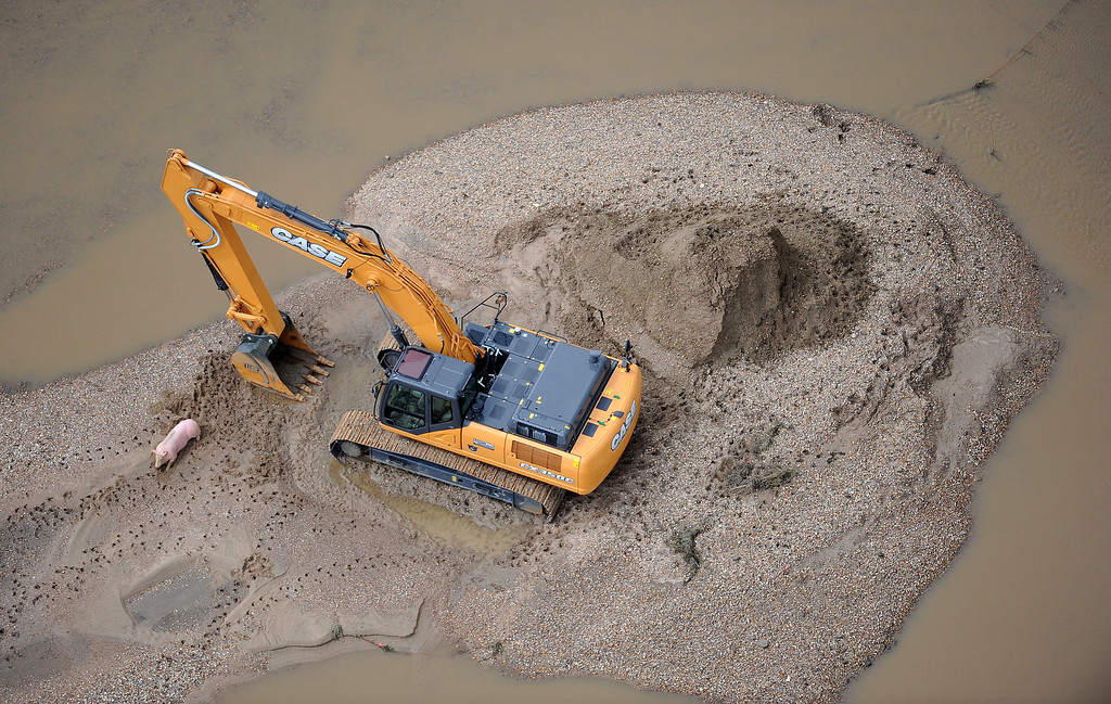 Description of . A pig and a track hoe are stranded on a sanding island in flooded land near Milliken, Colorado, on Monday, September 16, 2013.  (Photo By Tim Rasmussen/The Denver Post)