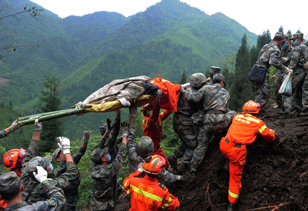 Description of . This photo taken on April 25, 2013 shows rescuers carrying a victim's body in Taiping township in Lushan county of Yaan, southwest China's Sichuan province.  Tens of thousands of homeless survivors of China's devastating quake are living in makeshift tents or on the streets, facing shortages of food and supplies as well as an uncertain future.  AFP/Getty Images