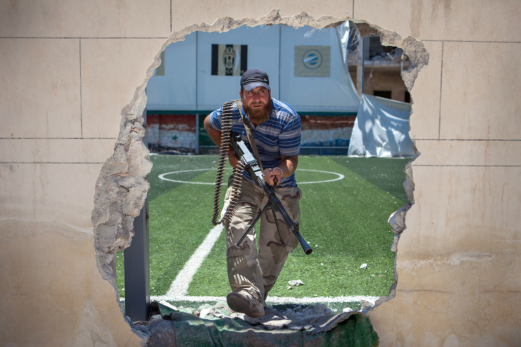 Description of . A rebel fighter passes through an access hole broken in the perimeter of a football pitch, close to the front line, where clashes between the rebels and pro-government troops have been taking place on the outskirts of the northern city of Aleppo, on July 4, 2013. Syria's President Bashar al-Assad accused the West of sending