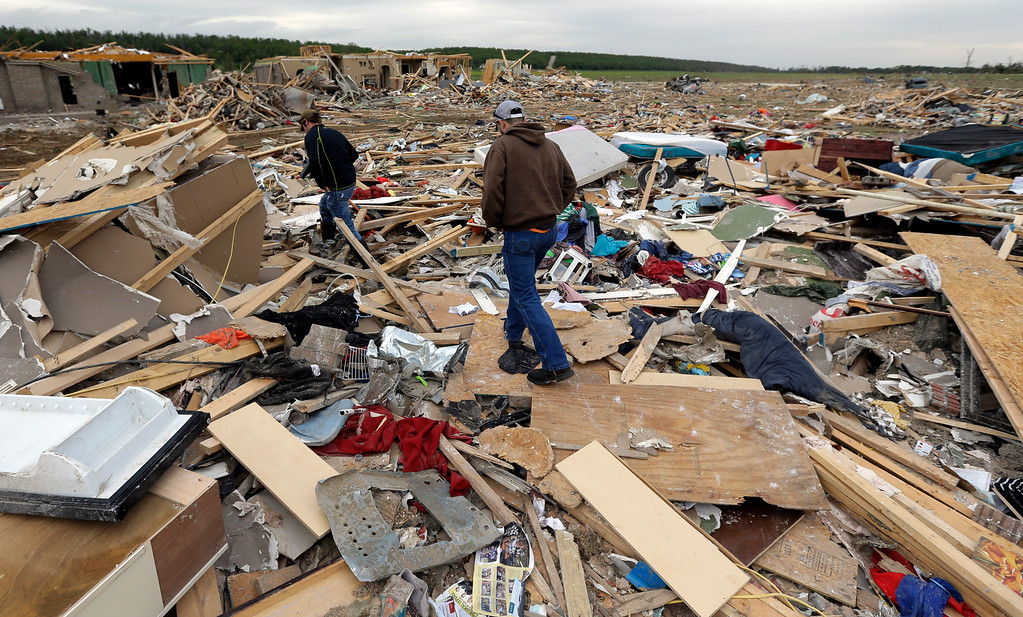 Description of . Austin Hargrove, left, and Ryan Williams, right, survey damage to a friends home that was destroyed by Sunday's tornado, Tuesday, April 29, 2014, in Vilonia, Ark.   (AP Photo/Eric Gay)