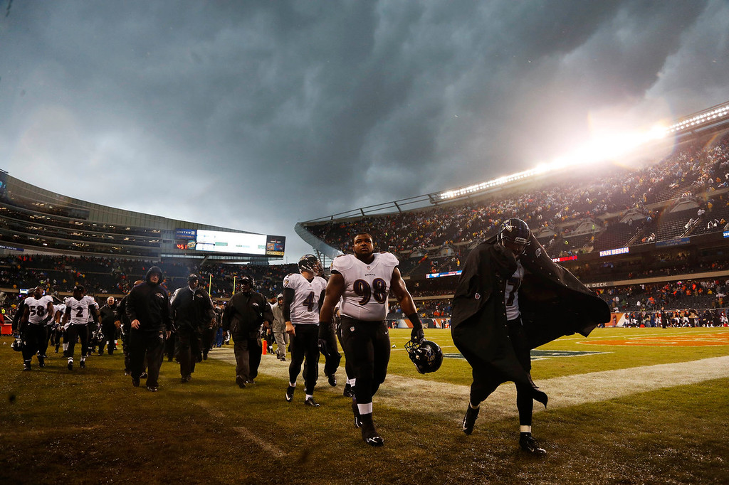 Description of . Baltimore Ravens players leave the field as play was suspended for a severe thunderstorm blowing through Soldier Field during the first half of an NFL football game against the Chicago Bears, Sunday, Nov. 17, 2013, in Chicago. (AP Photo/Charles Rex Arbogast)