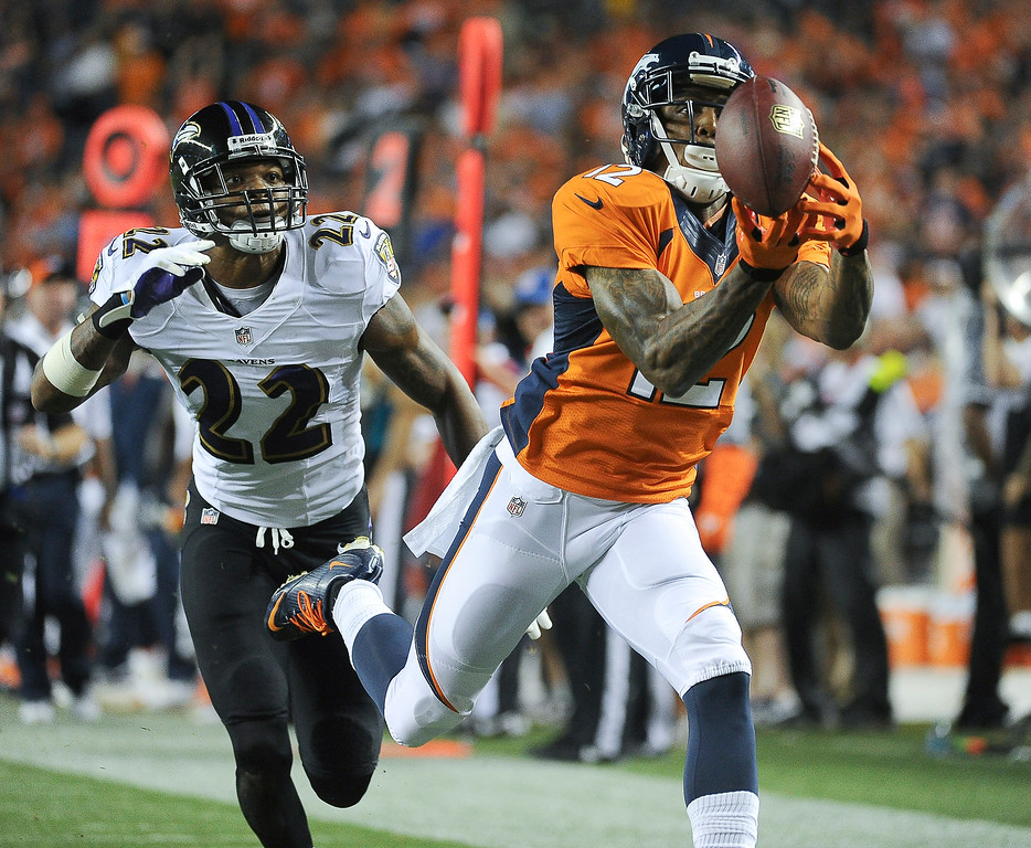 Description of . Denver Broncos wide receiver Andre Caldwell (12) catches a pass for a touchdown in the third quarter. The Denver Broncos took on the Baltimore Ravens in the first game of the 2013 season at Sports Authority Field at Mile High in Denver on September 5, 2013. (Photo by Tim Rasmussen/The Denver Post)