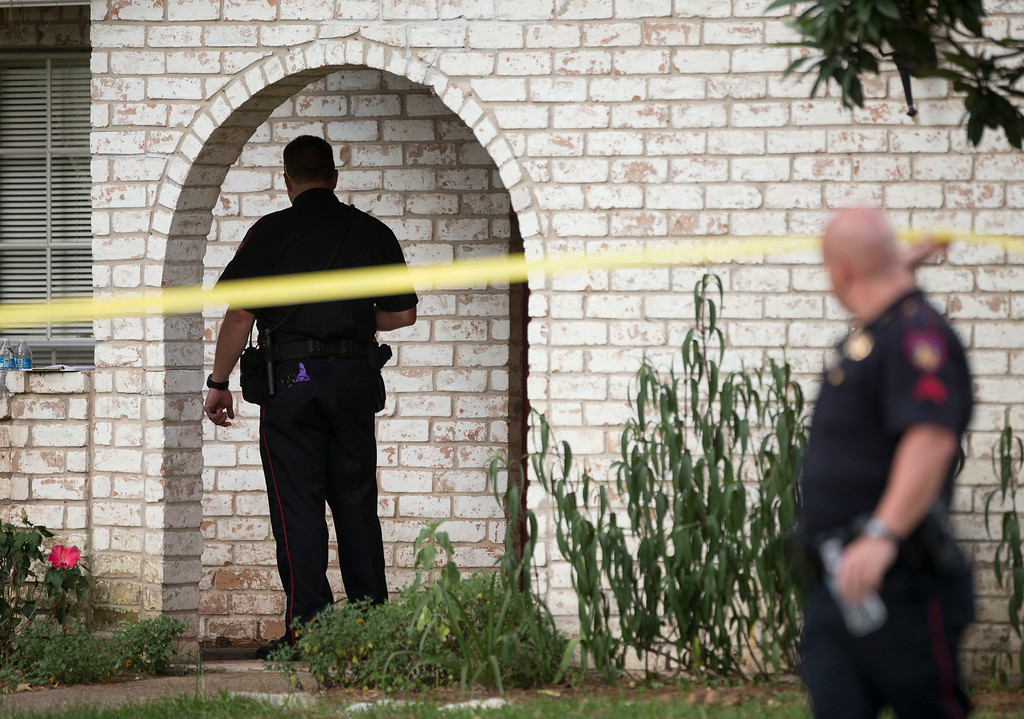 Description of . Law enforcement officers investigate the scene of a shooting Wednesday, July 9, 2014, in Spring, Texas. A Harris County Sheriff's Office statement says precinct deputy constables were called to a house about 6 p.m. Wednesday and found two adults and three children dead. Another child later died at a hospital. (AP Photo/Houston Chronicle, Brett Coomer)