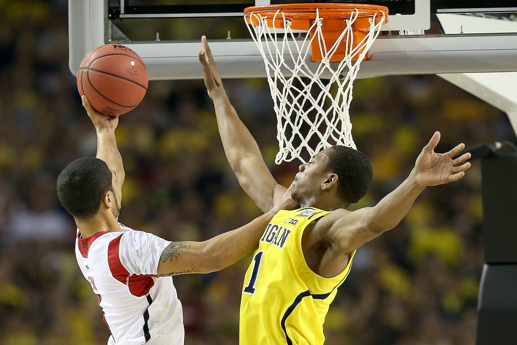 Description of . Peyton Siva #3 of the Louisville Cardinals drives for a shot attempt in the first half against Glenn Robinson III #1 of the Michigan Wolverines during the 2013 NCAA Men\'s Final Four Championship at the Georgia Dome on April 8, 2013 in Atlanta, Georgia.  (Photo by Streeter Lecka/Getty Images)
