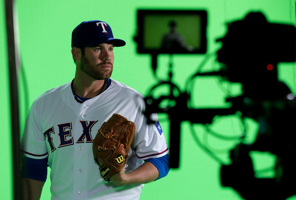 Description of . Texas Rangers starting pitcher Colby Lewis poses for photoghraphers during photo day at baseball spring training  Wednesday, Feb. 20, 2013, in Surprise, Ariz. (AP Photo/Charlie Riedel)