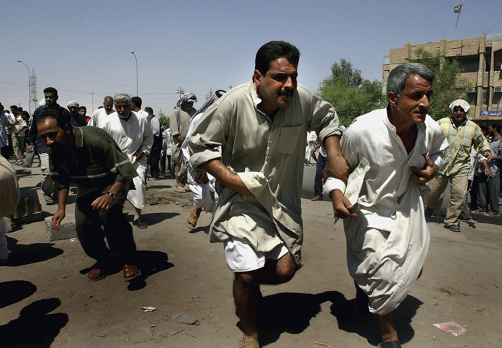 . Iraqi Shiite demonstrators flee from unknown gunmen as bullets fly overhead on August 26, 2004 in Najaf, Iraq. The Shiite demonstration came under fire whilst en route to the Imam Ali Shrine, further inflaming a situation already tense after at least 25 people were killed in a suspected mortar attack on a mosque filled with protesters preparing to travel to Najaf, August 26, in Kufa, Iraq. (Photo by Ghaith Abdul-Ahad/Getty Images).