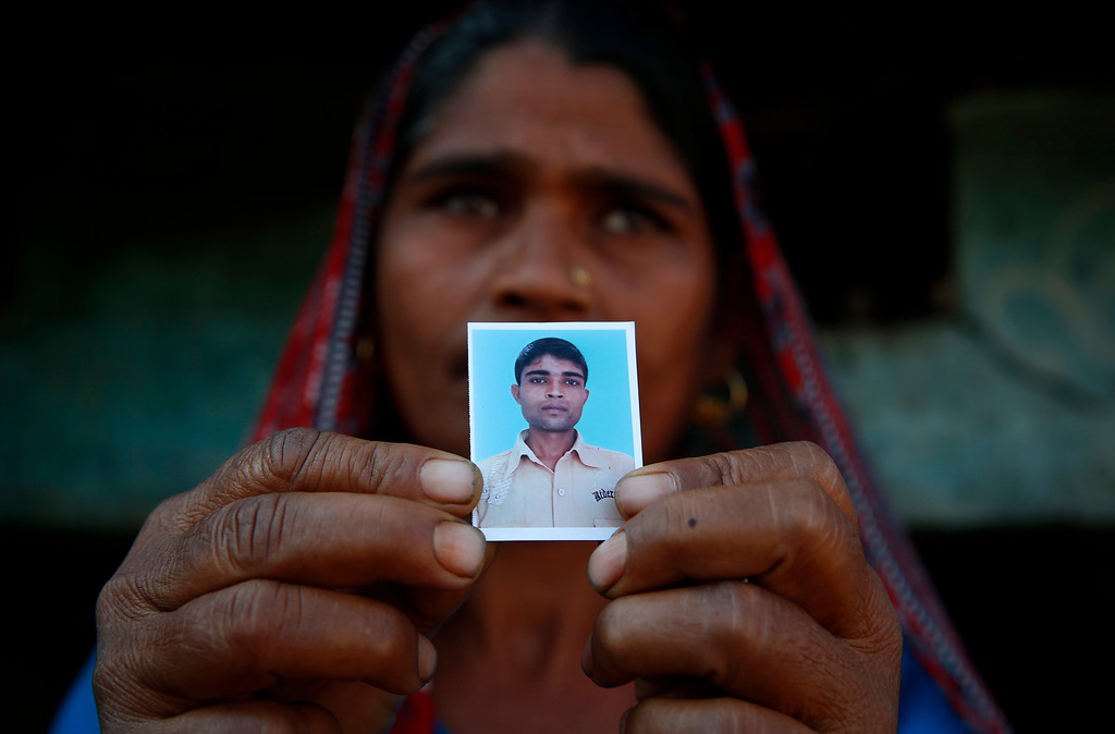 Description of . In this Wednesday, Feb. 12, 2014 photo, Taravati, who uses only one name, shows a photograph of her son Shiv Kumar Singh, a daily wage laborer, who was killed by a tiger at Maniawala, in northern India. The tiger that killed Singh on Jan. 10 has killed at least nine people so far traveling over 120 miles of villages, small towns and even a highway, spreading fear amongst the villagers many of whom are either farmers or laborers working the the large swathes of sugarcane fields which need harvesting now. (AP Photo/Saurabh Das)