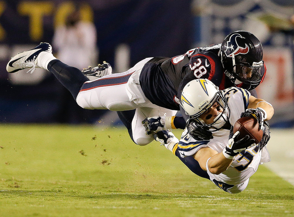 Description of . San Diego Chargers running back Danny Woodhead dives for extra yard under pressure from Houston Texans free safety Danieal Manning during the first half of an NFL football game Monday, Sept. 9, 2013, in San Diego. (AP Photo/Gregory Bull)